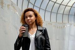 Una bella giovane donna afroamericana moderna in un bomber tiene un vetro nero nella mano contro lo sfondo di una o fotografia stock