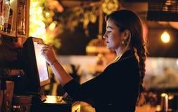 Una bella giovane donna allo scrittorio in un ristorante fotografie stock libere da diritti