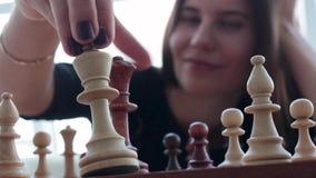 Una bella giovane donna castana di Latina con un sorriso a trentadue denti meraviglioso che gioca scacchi a casa video d archivio