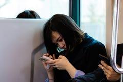 Una bella giovane donna che esamina il suo telefono mentre viaggiando sul treno fotografia stock