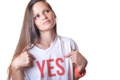 Una bella giovane donna che indica alla parola sul suo t-shir bianco Immagine Stock Libera da Diritti