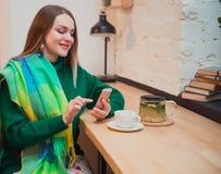 Una bella giovane donna con capelli biondi sta sedendosi in un caffè negozio Acquisto in linea Beve il tè delizioso fotografie stock libere da diritti