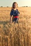 Una bella giovane donna con capelli lunghi che stanno nel giacimento di grano Immagini Stock Libere da Diritti