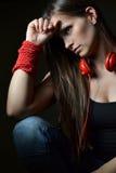 Una bella giovane donna con le cuffie rosse Fotografia Stock