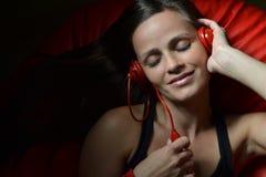 Una bella giovane donna con le cuffie rosse Fotografie Stock Libere da Diritti