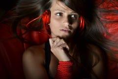 Una bella giovane donna con le cuffie rosse Immagini Stock