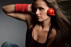 Una bella giovane donna con le cuffie rosse Immagine Stock