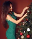 Una bella giovane donna orientale che decora l'albero di Natale Fotografia Stock
