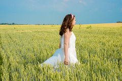 Una bella giovane donna su un giacimento di grano Fotografia Stock Libera da Diritti