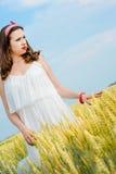 Una bella giovane donna su un giacimento di grano Immagini Stock Libere da Diritti
