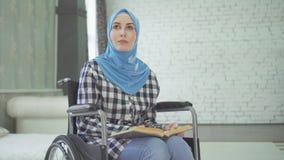 Una bella giovane donna in un hijab è cieca o debolmente imponente, una sedia a rotelle leggente una fonte di Braille fotografia stock libera da diritti