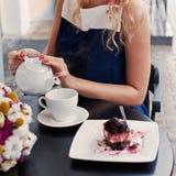 Una bella giovane ragazza bionda in vestito da estate alla tavola in pav Fotografia Stock Libera da Diritti