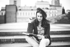Una bella, giovane ragazza caucasica che si siede sul sorriso della via, la gioia, si siede con il taccuino e la penna in Ruhi In Fotografia Stock Libera da Diritti