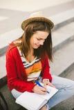 Una bella, giovane ragazza caucasica che si siede sul sorriso della via, la gioia, si siede con il taccuino e la penna in Ruhi In Immagini Stock