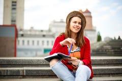 Una bella, giovane ragazza caucasica che si siede sul sorriso della via, la gioia, si siede con il taccuino e la penna in Ruhi In Immagine Stock