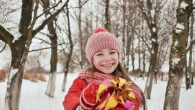 Una bella giovane scolara che sta in una foresta nevosa nell'inverno prende un regalo allegro dalle mani di un amico stock footage