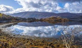 Una bella immagine di specchio del cielo al lago Sunart negli altopiani della Scozia fotografia stock