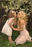 Una bella madre bionda con una piccola ragazza della figlia che rannicchia sul fondo della natura dei fiori verdi e porpora e del Fotografie Stock