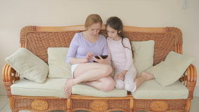 Una bella madre e la sua piccola conversazione della figlia bene, la madre tiene una compressa ed insegna a sua figlia archivi video