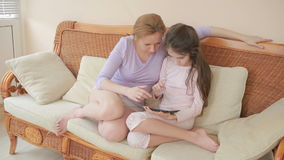 Una bella madre e la sua piccola conversazione della figlia bene, la madre tiene una compressa ed insegna a sua figlia video d archivio