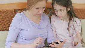Una bella madre e la sua piccola conversazione della figlia bene, la madre tiene una compressa ed insegna a sua figlia stock footage