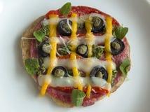 Una bella, mini-pizza variopinta su un fondo bianco Fotografia Stock