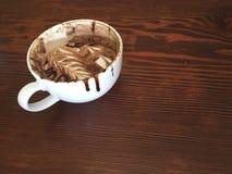 Una bella moca con i turbinii di arte e del cioccolato della schiuma, su un fondo di legno Immagini Stock Libere da Diritti
