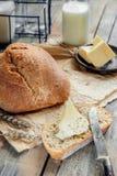 Una bella pagnotta del pane di lievito naturale da grano bianco su un piatto su un bordo di tela Pasticcerie casalinghe fotografia stock libera da diritti