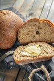 Una bella pagnotta del pane di lievito naturale da grano bianco su un piatto su un bordo di tela Pasticcerie casalinghe fotografie stock