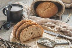 Una bella pagnotta del pane di lievito naturale da grano bianco su un piatto su un bordo di tela Pasticcerie casalinghe fotografia stock