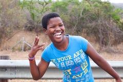 Una bella ragazza africana felice in maglietta blu che sorride con i denti bianchi e la gomma da masticare all'aperto vicini su fotografia stock