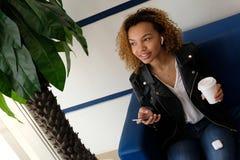 Una bella ragazza afroamericana con un ricevitore telefonico bianco in suo orecchio sta cercando la palma Telefono e vetro bianco fotografia stock