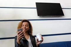 Una bella ragazza afroamericana in un rivestimento nero con i airpods in suo orecchio sorride e tiene un vetro bianco e guarda immagini stock