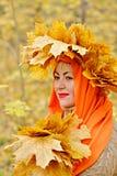 Una bella ragazza bionda di mezza età in una corona delle foglie gialle in una sciarpa arancio sta stando nella foresta, tenente immagini stock