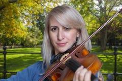 Una bella ragazza bionda in vestito nero con le labbra rosse gioca un violino fotografia stock