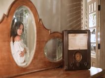 Una bella ragazza cammina dopo una tavola con una radio ed i sorrisi nello specchio stock footage