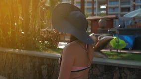 Una bella ragazza in cappello blu va alla città tropicale Estate Sun video d archivio