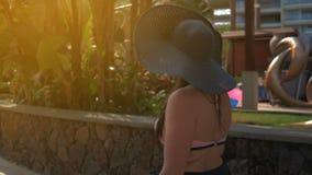 Una bella ragazza in cappello blu va alla città tropicale Estate Sun Rallentatore video d archivio