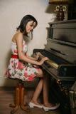 Una bella ragazza castana sta giocando il piano Fotografie Stock Libere da Diritti