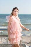 Una bella ragazza che posa su un balcone trasparente su un fondo blu del mare Una signora in un vestito rosa con le ruche vicino  fotografia stock