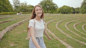 Una bella ragazza con capelli lunghi e uno zaino sul suo indietro correre lungo uno stadio verde, godente della natura e stock footage