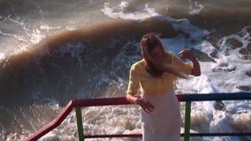 Una bella ragazza con capelli lunghi, un vestito bianco gialla sta e raddrizza i suoi capelli sulla piattaforma d'esame, punti archivi video
