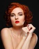 Una bella ragazza con capelli rossi esamina ansiosamente la macchina fotografica Immagini Stock