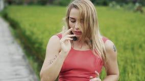 Una bella ragazza con capelli scorrenti con i tatuaggi sulle sue mani sta ballando sul campo verde, delicatamente e sensuale archivi video