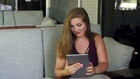 Una bella ragazza con peso in eccesso si siede in un ristorante con una compressa video d archivio