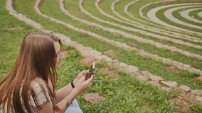 Una bella ragazza con un telefono cellulare in sue mani si siede sull'erba in mezzo di grande stadio verde ricreazione archivi video