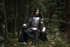 Una bella ragazza del guerriero con un chainmail d'uso della spada ed armatura in una foresta misteriosa fotografia stock