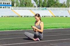 Una bella ragazza di forma fisica in abiti sportivi grigi utilizza lo smartphone ed ascolta musica allo stadio dopo l'allenamento immagini stock libere da diritti