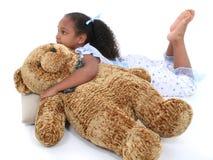 Una bella ragazza di sei anni che indica in pigiami con l'orso Immagine Stock