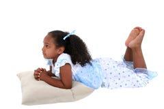 Una bella ragazza di sei anni che indica in pigiami sopra bianco Fotografia Stock